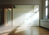 Room with beams of sunlight through glass wall