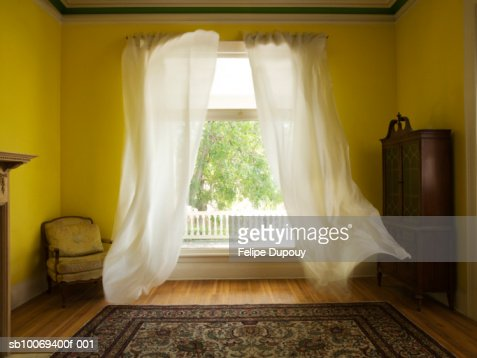 Room with curtains billowing at open window : Stock Photo