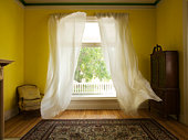Room with curtains billowing at open window