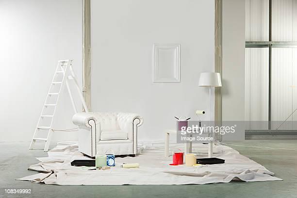 Chambre avec des pots de peinture blanche et fauteuil