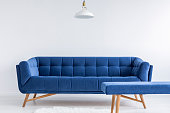 Ascetic white room with lamp, blue vintage sofa and bench