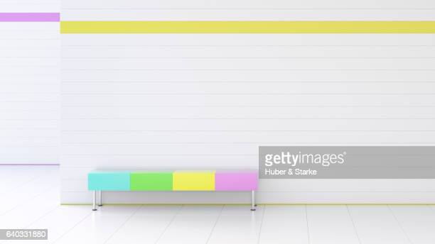 room with white tiles and a colourful bench