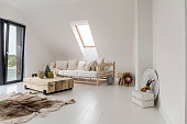 White spacious room with stylish wooden furniture and roof window
