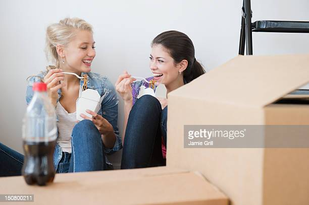 Roommates eating takeout on move in day
