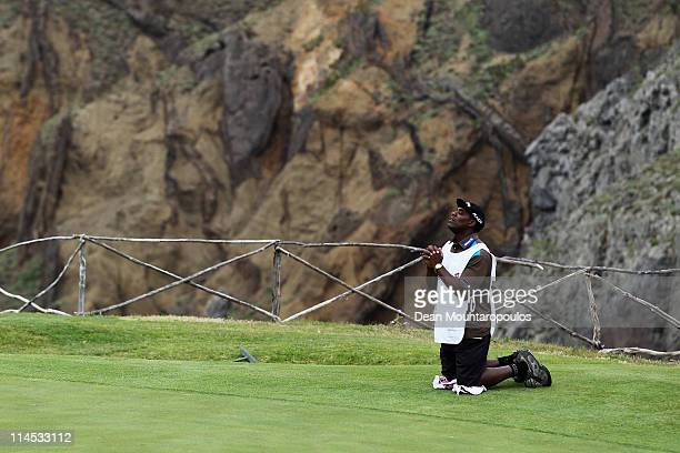 Roope Kakko of Finland's caddie Hugo Benson kneels down on the 14th green and prays during the final day of the Madeira Islands Open on May 22 2011...
