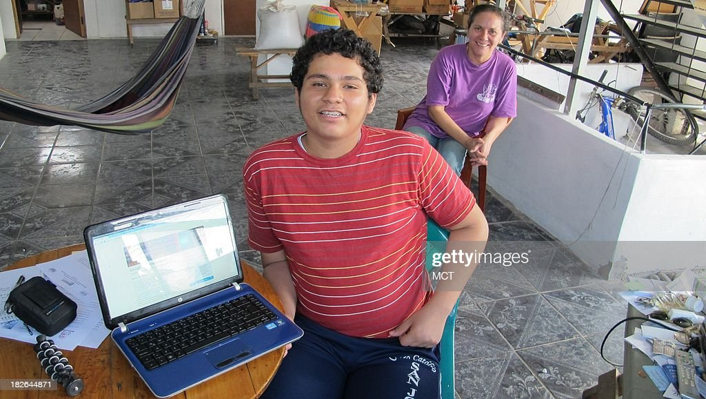 Roosemberth Palacios, 16, sits in his Armenia, El Salvador, home Sept. 19, 2013, near his laptop computer that he uses for taking online university courses. His mother, Giovanna Valverde, looks on.