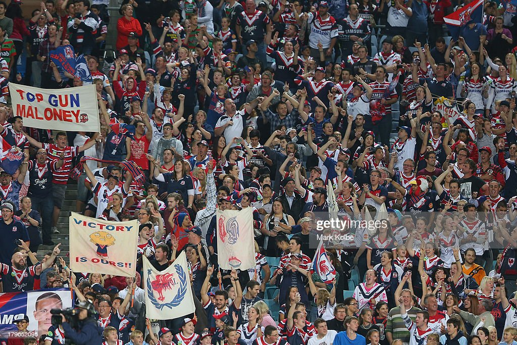 Roosters supporters in the crowd cheer during the round 26 NRL match between the South Sydney Rabbitohs and the Sydney Roosters at ANZ Stadium on September 6, 2013 in Sydney, Australia.