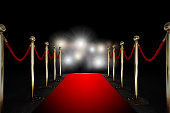 Red carpet between two rope barriers and flash light