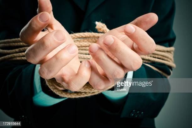 Rope Binding a Businessman's Hands