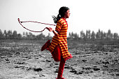 Village girl playing with jumping rope in playground.