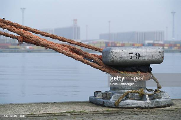 Rope tied to mooring on quayside, close-up
