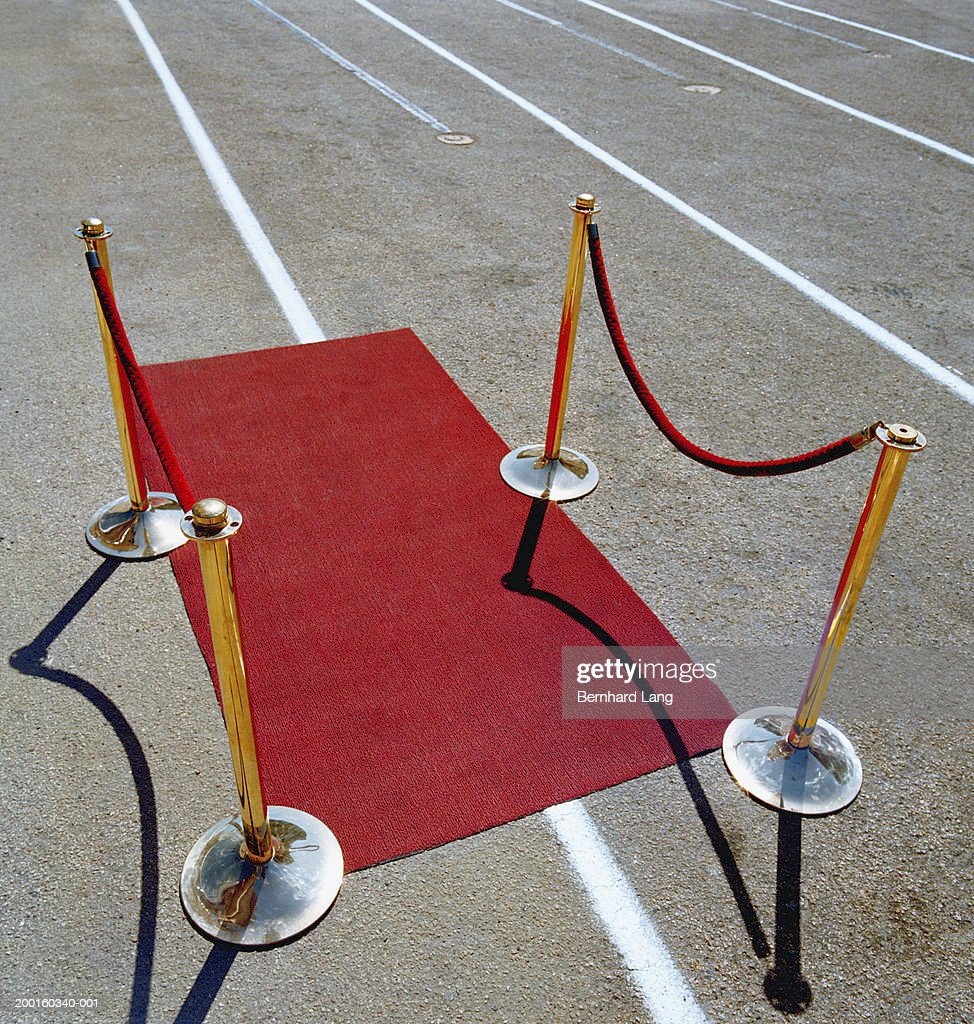 Roped barriers by red carpet on runway : Stock Photo