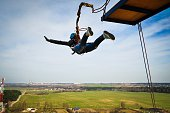 Ropejumping: girl jumping from a height in the equipment for mountaineering and helmet