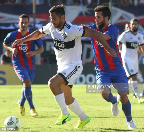 Roque Santa Cruz of Olimpia fights for the ball with Mauricio Victorino during a match between Olimpia and Cerro Porteño as part of the 17th round of...