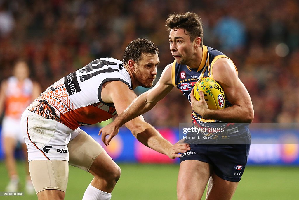 Rory Atkins of the Crows gets away from Shane Mumford of the Giants during the round 10 AFL match between the Adelaide Crows and the Greater Western Sydney Giants at Adelaide Oval on May 28, 2016 in Adelaide, Australia.