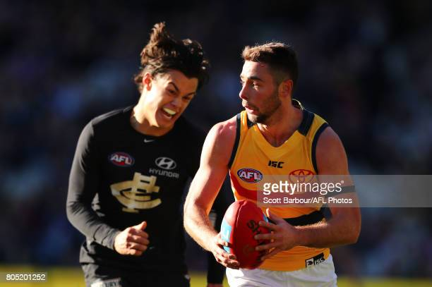 Rory Atkins of the Crows is chased by Jack Silvagni of the Blues during the round 15 AFL match between the Carlton Blues and the Adelaide Crows at...