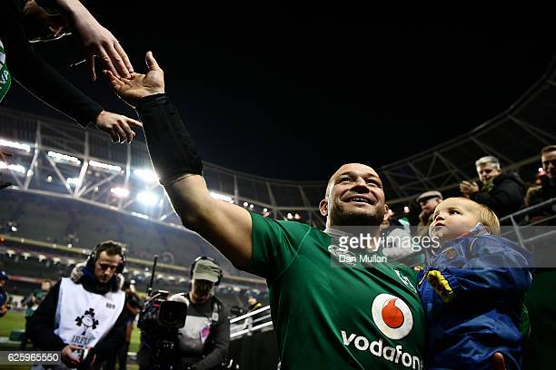 Rory Best of Ireland leaves the field with his son Richie following his 100th cap and his side's victory during the international match between...