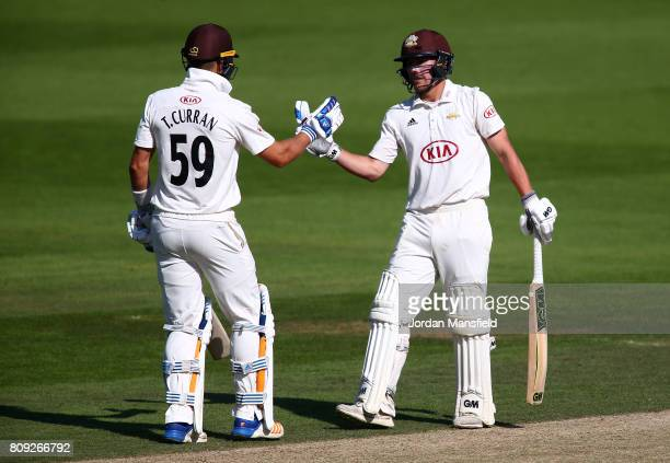 Rory Burns of Surrey celebrates his 150 with Tom Curran of Surrey during day three of the Specsavers County Championship Division One match between...