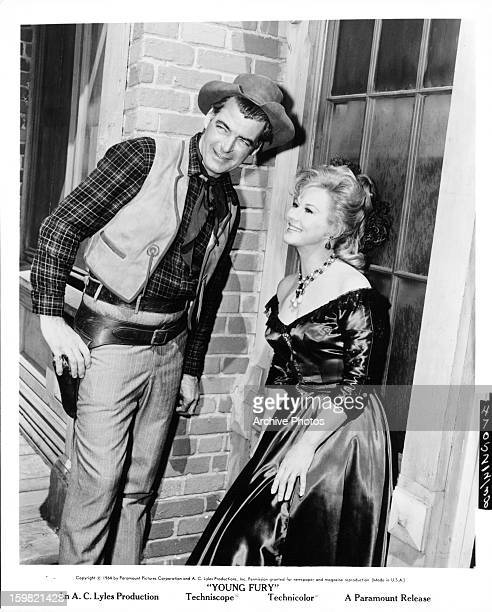 Rory Calhoun and Virginia Mayo smiling in a scene from the film 'Young Fury' 1965