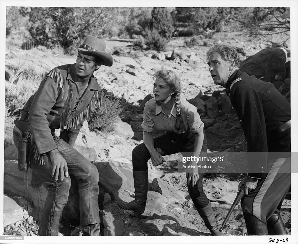 Rory Calhoun Peggie Castle and man crouching down in a defensive stance in a scene from the film 'The Yellow Tomahawk' 1954