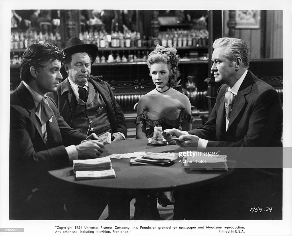 Rory Calhoun plays David Brian a game of cards while Edgar Buchanan and Piper Laurie watch in a scene from the film 'Dawn At Socorro' 1954
