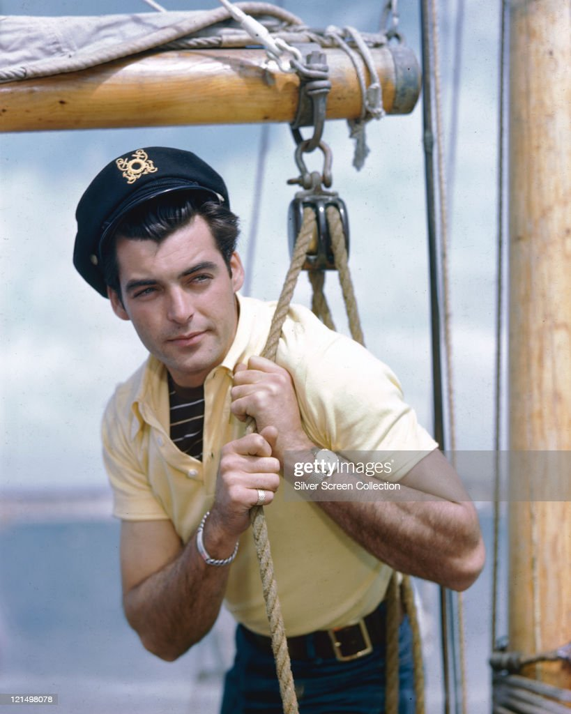 Rory Calhoun US actor wearing a striped tshirt beneath a yellow polo shirt and a sailor's cap as he pulls a rope through a pulley on a yacht circa...