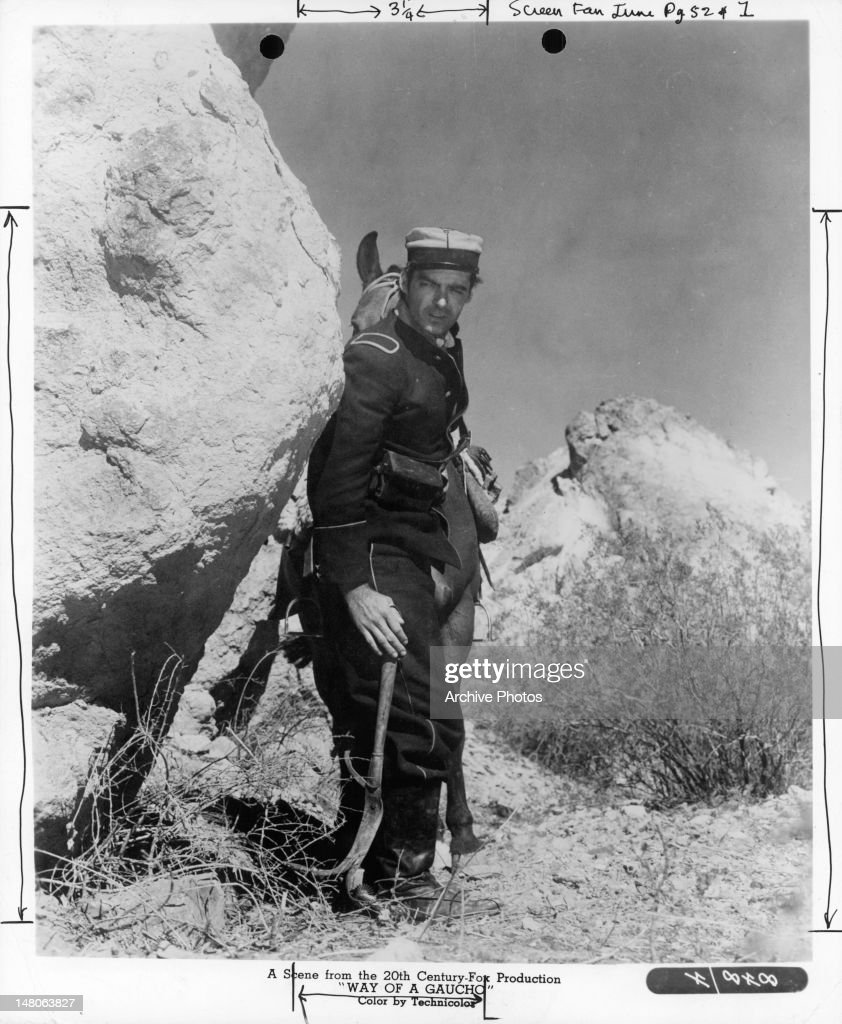 Rory Calhoun walking through a rocky mountain on foot leading his horse behind him in a scene from the film 'Way Of Gaucho' 1952