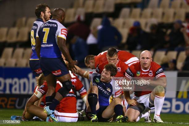 Rory Kostjasyn of the Cowboys celebrates victory with his team mates as Michael Weyman of the Dragons looks dejected during the round 14 NRL match...