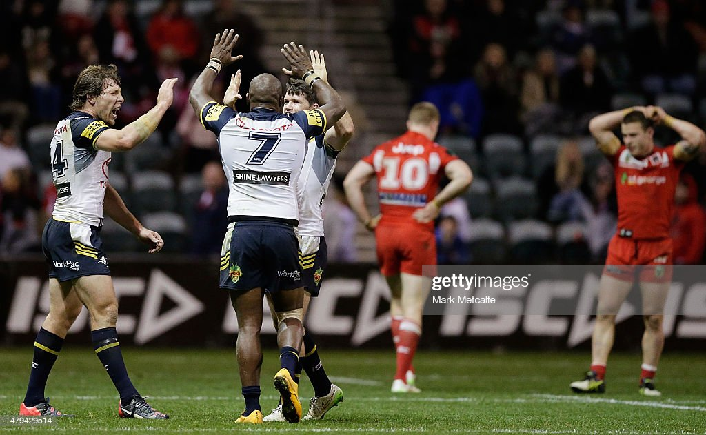 Rory Kostjasyn Robert Lui and Lachlan Coote of the Cowboys celebrate victory in the round 17 NRL match between the St George Illawarra Dragons and...