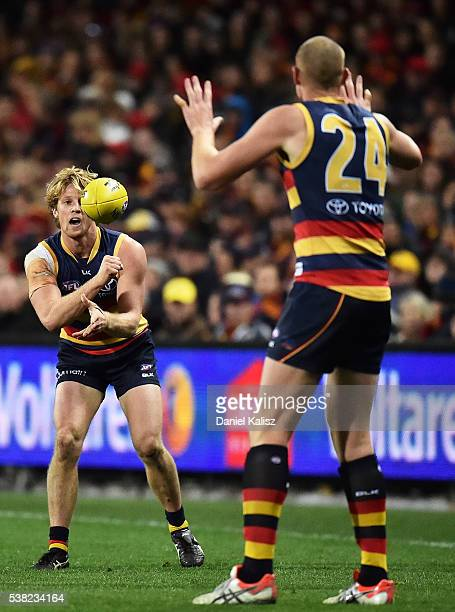 Rory Laird handballs to Sam Jacobs of the Crows during the round 11 AFL match between the Adelaide Crows and the St Kilda Saints at Adelaide Oval on...
