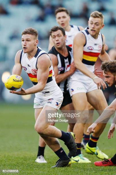 Rory Laird of the Crows handballs during the round 19 AFL match between the Collingwood Magpies and the Adelaide Crows at Melbourne Cricket Ground on...