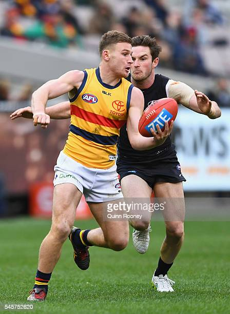 Rory Laird of the Crows handballs whilst being tackled Jed Lamb of the Blues during the round 16 AFL match between the Carlton Blues and the Adelaide...