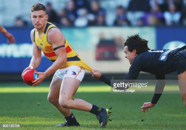 Rory Laird of the Crows is tackled by Jack Silvagni of the Blues during the round 15 AFL match between the Carlton Blues and the Adelaide Crows at...