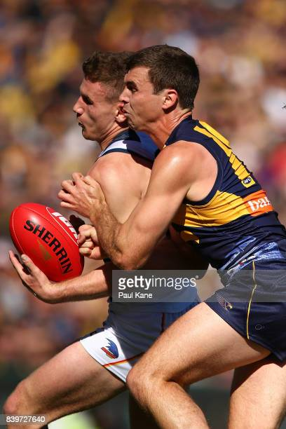 Rory Laird of the Crows takes the ball over the line against Jamie Cripps of the Eagles during the round 23 AFL match between the West Coast Eagles...