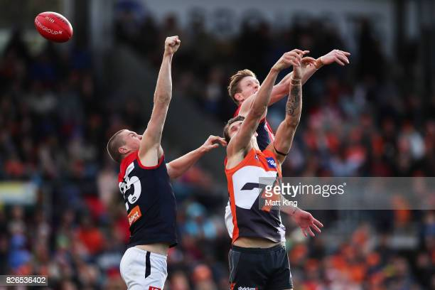 Rory Lobb of the Giants is challenged by Tom McDonald and Oscar McDonald of the Demons during the round 20 AFL match between the Greater Western...