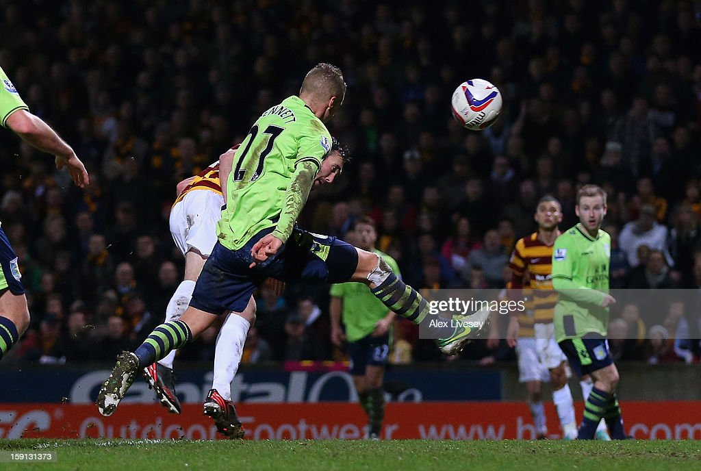 Rory McArdle of Bradford City gets a header past Joe Bennett of Aston Villa to score the second goal during the Capital One Cup Semi-Final 1st Leg match between Bradford City and Aston Villa at Coral Windows Stadium, Valley Parade on January 8, 2013 in Bradford, England.