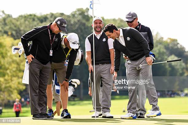 Rory McIlroy and Andy Sullivan of Team Europe laugh after McIlroy holed out for eagle from the sixth hole fairway during practice prior to the 2016...