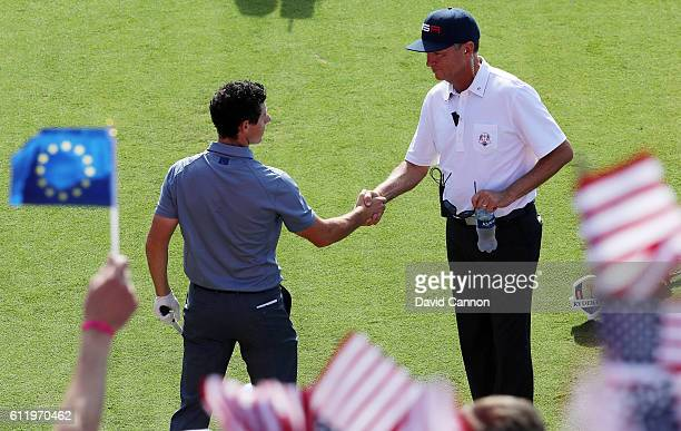 Rory McIlroy of Europe shakes hands with captain Davis Love III of the United States on the first tee during singles matches of the 2016 Ryder Cup at...