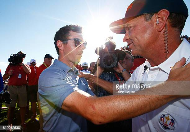 Rory McIlroy of Europe speaks to captain Davis Love III of the United States after the United States defeated Europe to win the Ryder Cup during...