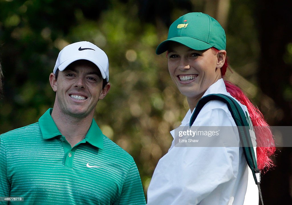 <a gi-track='captionPersonalityLinkClicked' href=/galleries/search?phrase=Rory+McIlroy&family=editorial&specificpeople=783109 ng-click='$event.stopPropagation()'>Rory McIlroy</a> of Northern Ireland alongside his caddie/girlfriend <a gi-track='captionPersonalityLinkClicked' href=/galleries/search?phrase=Caroline+Wozniacki&family=editorial&specificpeople=740679 ng-click='$event.stopPropagation()'>Caroline Wozniacki</a> during the 2014 Par 3 Contest prior to the start of the 2014 Masters Tournament at Augusta National Golf Club on April 9, 2014 in Augusta, Georgia.