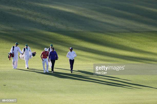 Rory McIlroy of Northern Ireland amatuer Toto Gana of Chile and amateur Curtis Luck of Australia walk down the first fairway during a practice round...