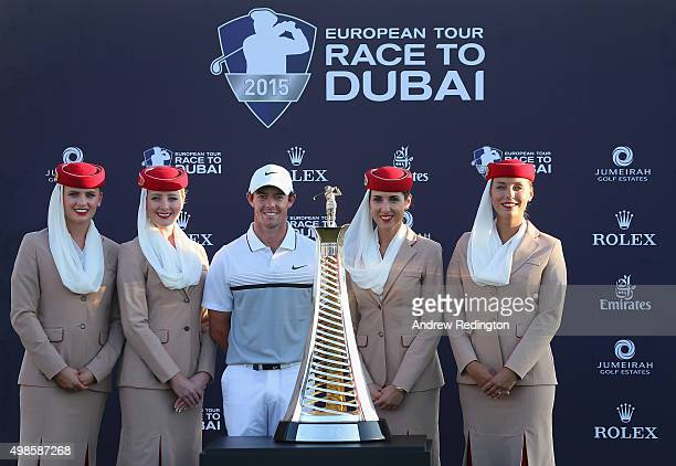 Rory McIlroy of Northern Ireland and cabin crew from Emirates Airlines poses with the Race To Dubai trophy following the final round of the DP World...