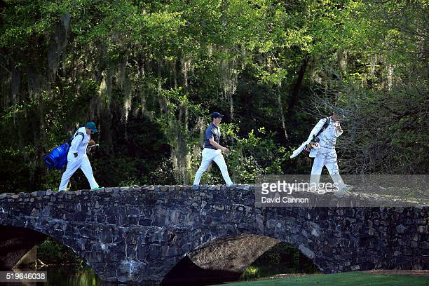 Rory McIlroy of Northern Ireland and caddie JP Fitzgerald walk across the Nelson bridge from the 12th green to the 13th tee during the first round of...