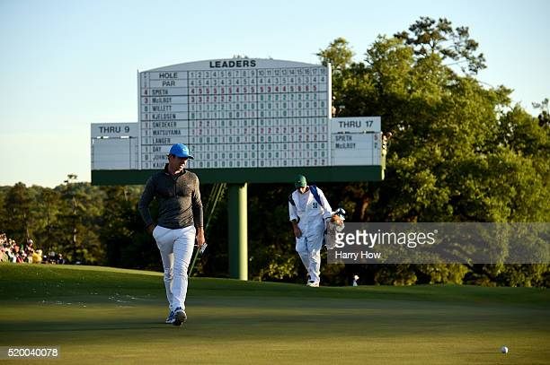 Rory McIlroy of Northern Ireland and caddie JP Fitzgerald walk on the 18th green during the third round of the 2016 Masters Tournament at Augusta...