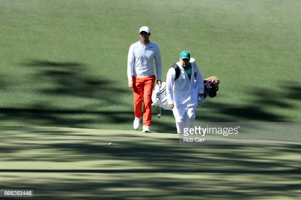 Rory McIlroy of Northern Ireland and caddie JP Fitzgerald walk to the tenth hole green during the third round of the 2017 Masters Tournament at...