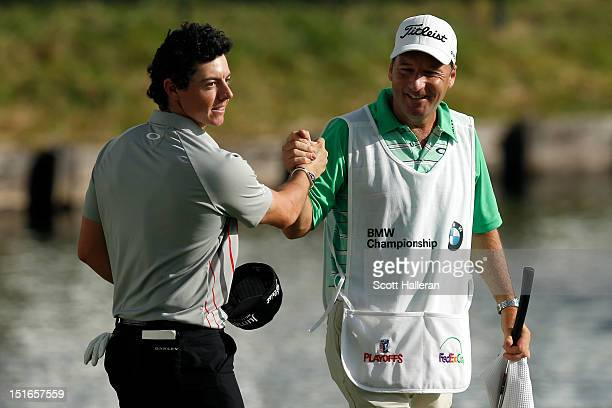 Rory McIlroy of Northern Ireland and his caddie JP Fitzgerald celebrate after McIroy finished the final round of the BMW Championship at 20 to win...