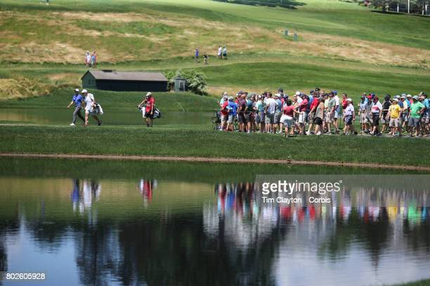 Rory McIlroy of Northern Ireland and his caddie JP Fitzgerald pass a water feature on their way to the sixteenth green during the fourth round of the...