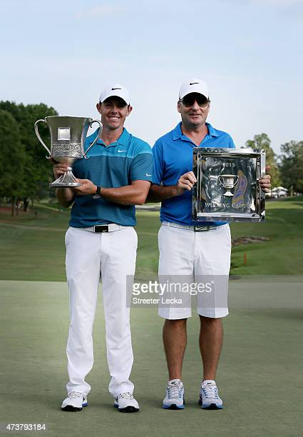 Rory McIlroy of Northern Ireland and his caddie JP Fitzgerald pose with the trophy after his win on the 18th hole during the final round at the Wells...