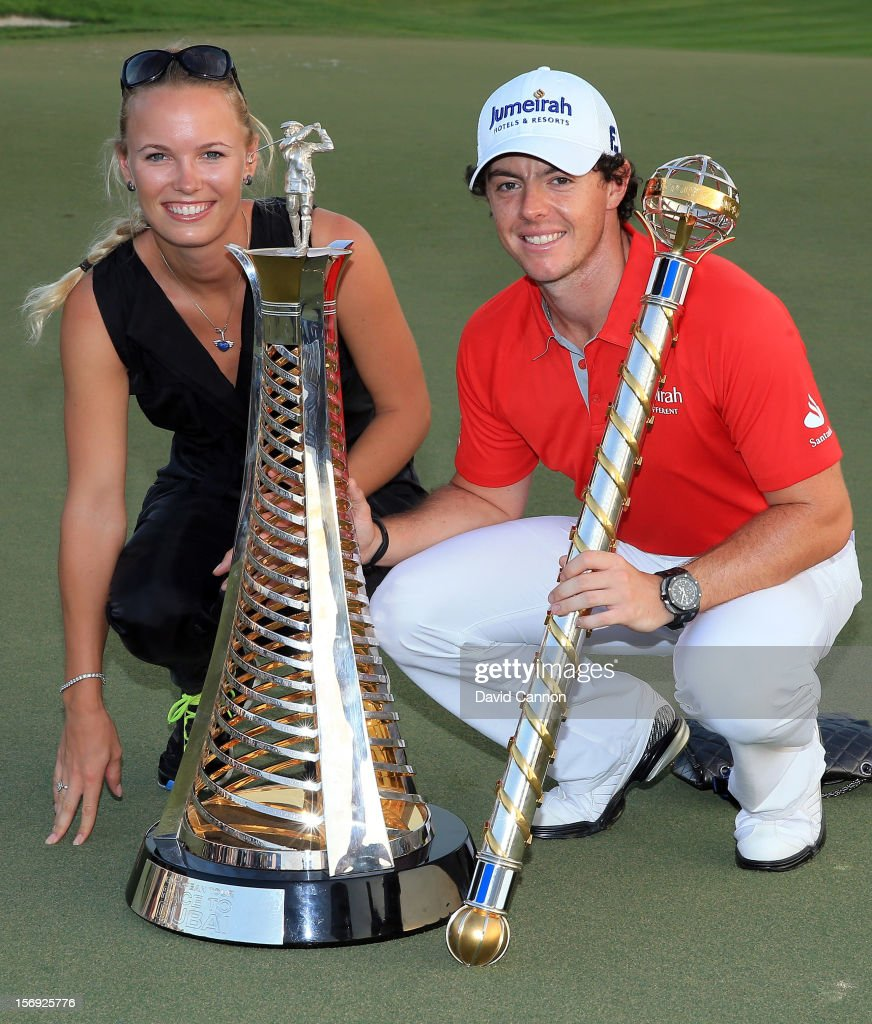 Rory McIlroy of Northern Ireland and his girlfriend <a gi-track='captionPersonalityLinkClicked' href=/galleries/search?phrase=Caroline+Wozniacki&family=editorial&specificpeople=740679 ng-click='$event.stopPropagation()'>Caroline Wozniacki</a> of Denmark with the DP World Tour Championship Trophy and the Race to Dubai Trophy (l) after his win during the final round of the 2012 DP World Tour Championship on the Earth Course at Jumeirah Golf Estates on November 25, 2012 in Dubai, United Arab Emirates.