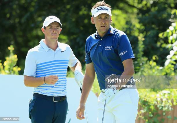 Rory McIlroy of Northern Ireland and Ian Poulter of England stand on the 13th tee during round three of The Northern Trust at Glen Oaks Club on...